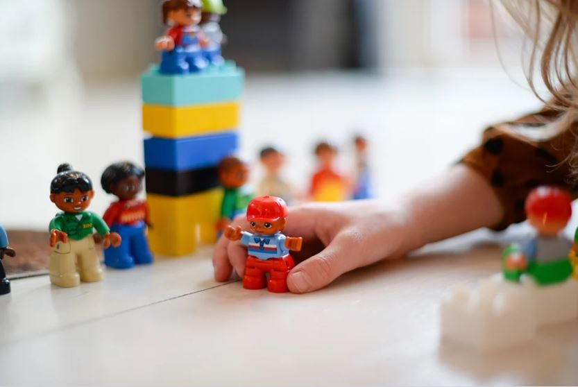 young girl child playing with toy figurines and colourful blocks